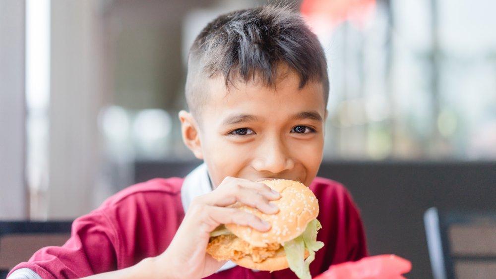 Teenager eating chicken sandwich