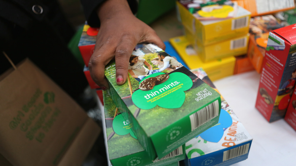 Hand grabbing Girl Scout cookie box