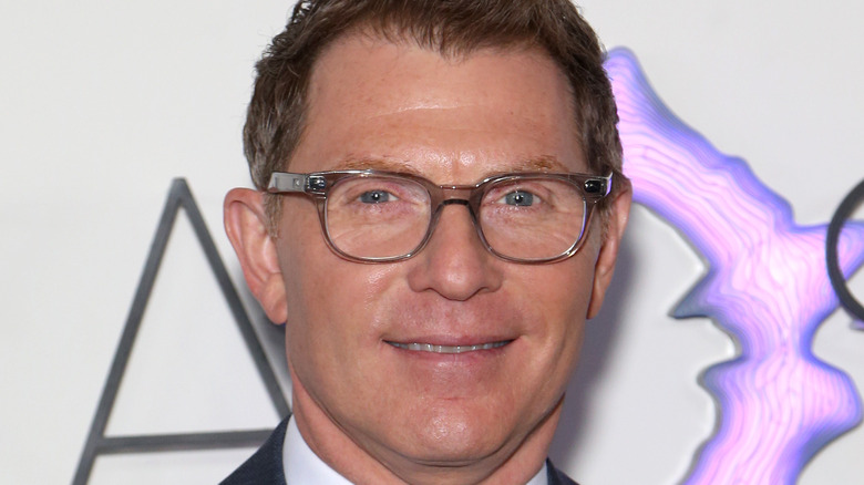 Bobby Flay wearing a suit and smiling
