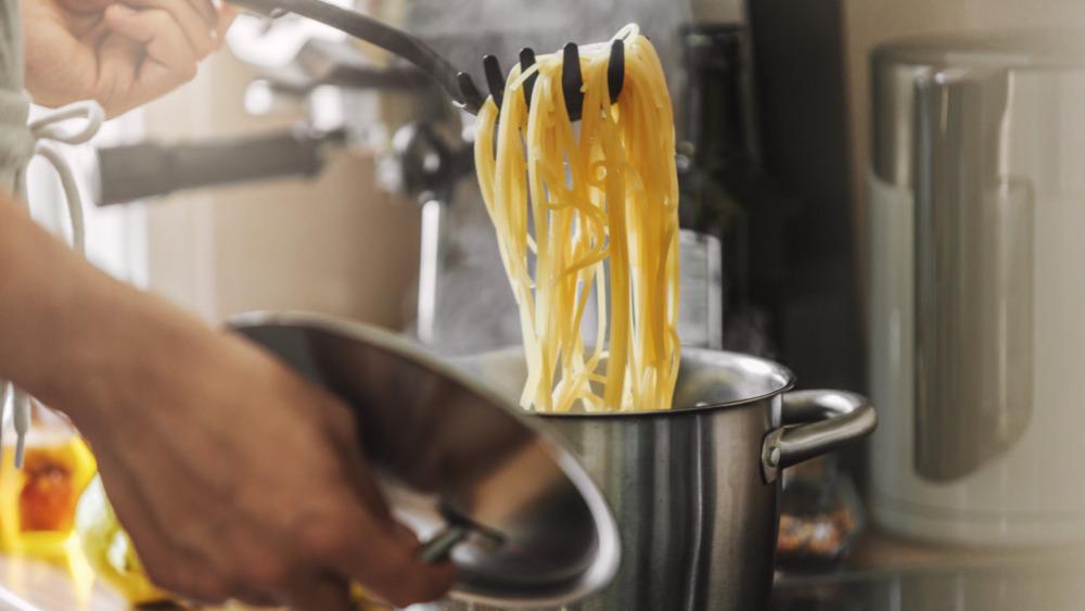 Person boiling pasta in a chrome pot