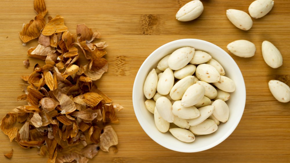 bowl of blanched almonds with almond skins on side