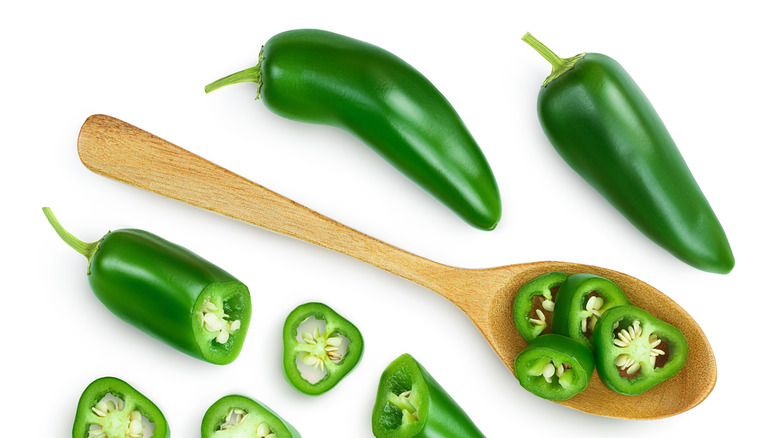 Whole jalapeños and slices with spoon.
