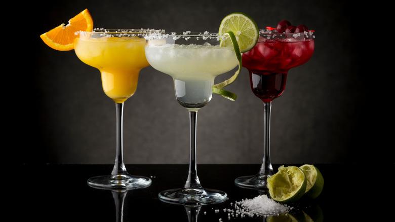 three margaritas with salted rims, lime margarita, orange margarita and cranberry margarita