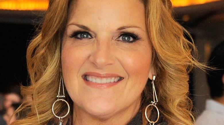 Trisha Yearwood smiles with dangling earrings