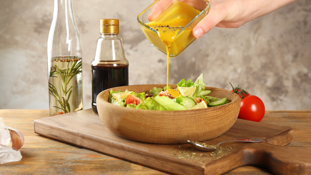 Woman pouring salad dressing
