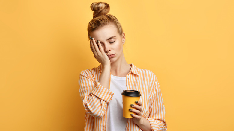 Tired woman holding cup of coffee