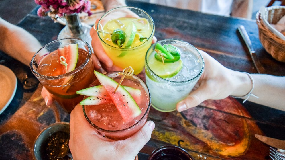 Hands holding up cocktails