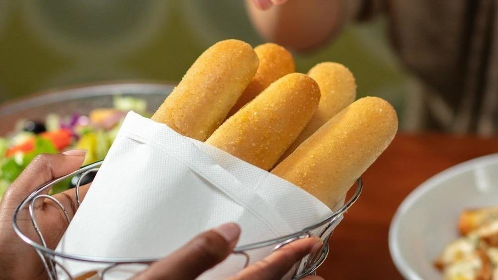 Hands holding basket of Olive Garden breadsticks
