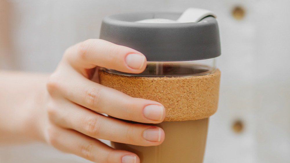 Hand holding reusable coffee cups