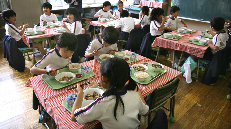 Japanese students eating lunch in classroom