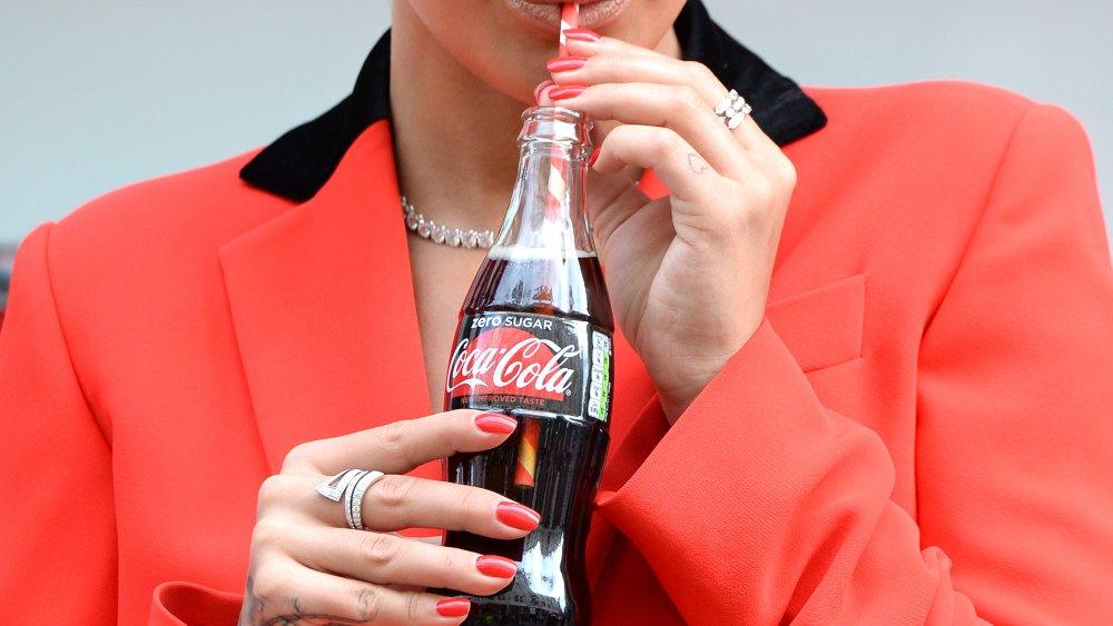 woman drinking coke zero out of a bottle