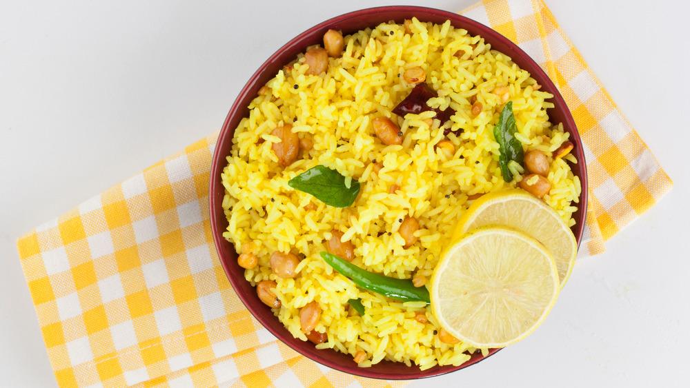 Bowl of yellow rice with lemon on napkin