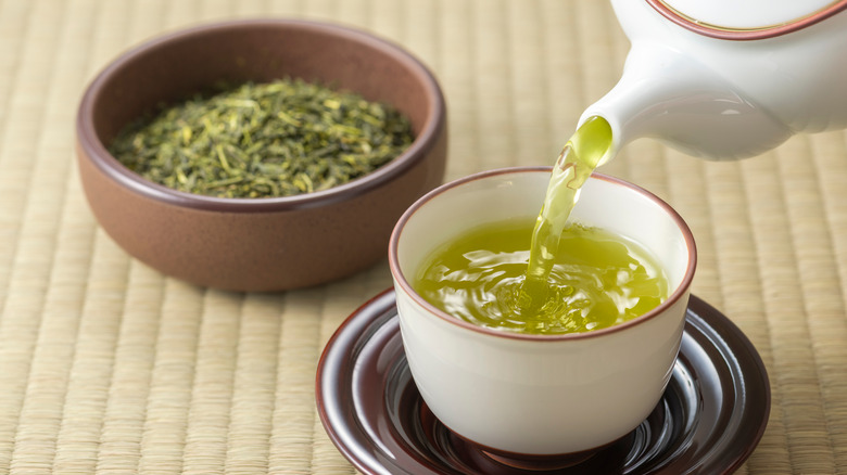 Green tea being poured into a cup with a bowl of green tea leaves in the background