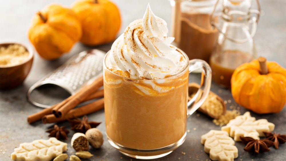 Pumpkin spice latte with whipped cream surrounded by pumpkins, cookies, and spices