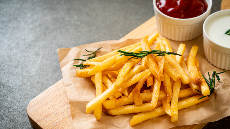 French fries and thyme atop a wooden board with two ramekins of dipping sauce
