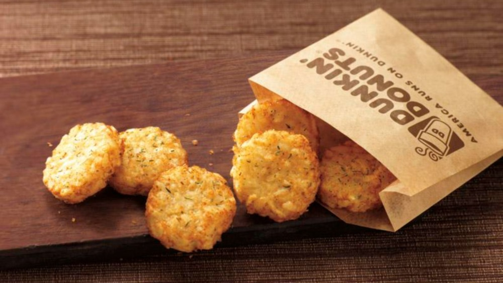 Dunkin' hash browns with paper sleeve and wooden board