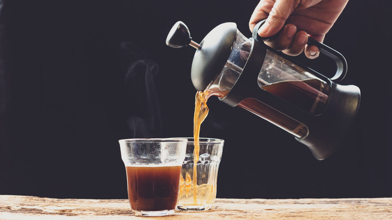 French press pouring coffee into cup