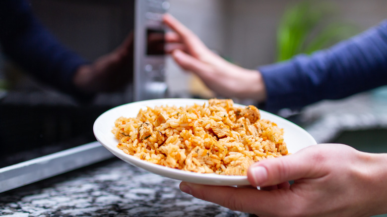 woman's hand holding bowl of rice to go in the microwave