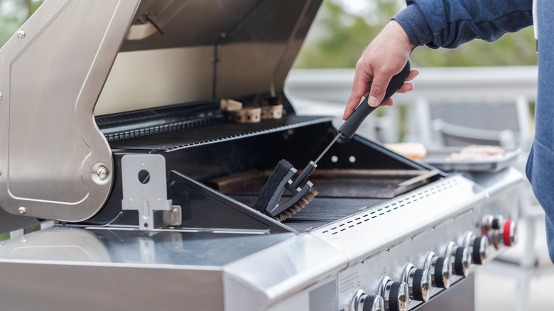 Man holding bristle brush while cleaning grill