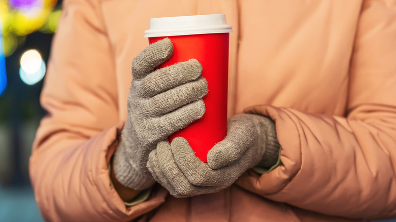 Gloved hands holding paper coffee cup