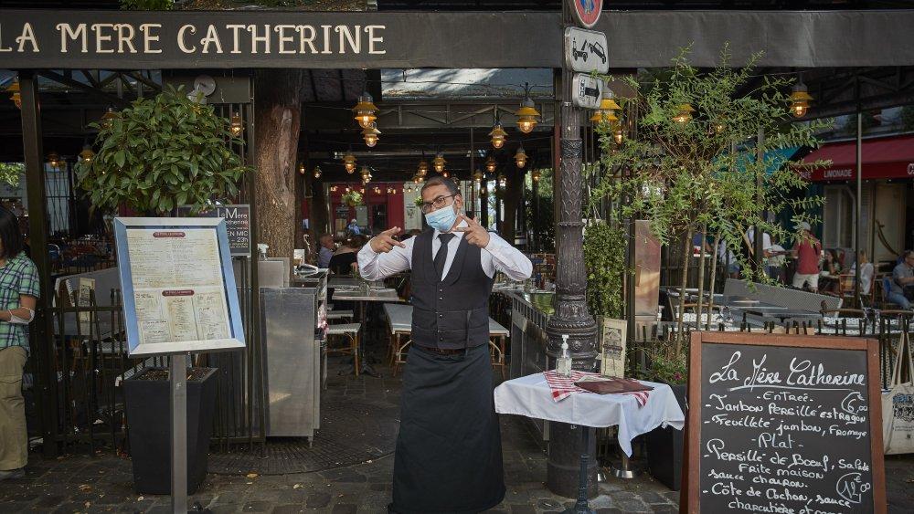 Waiter standing outside restaurant in France
