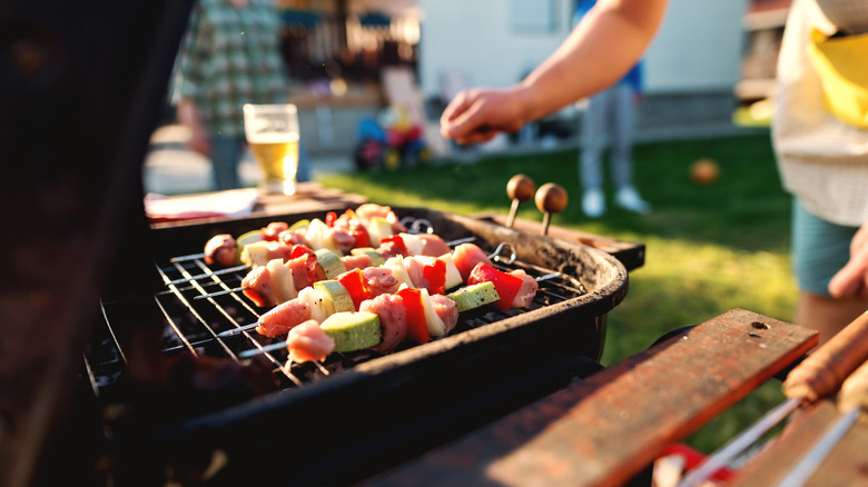 A person grilling kebabs on a black grill