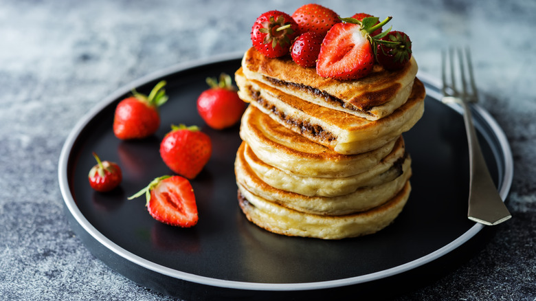 Stack of pancakes with Nutella and strawberries