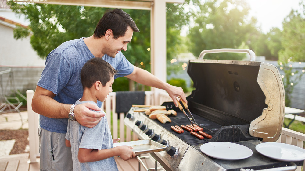 Child and adult grilling hot dogs together