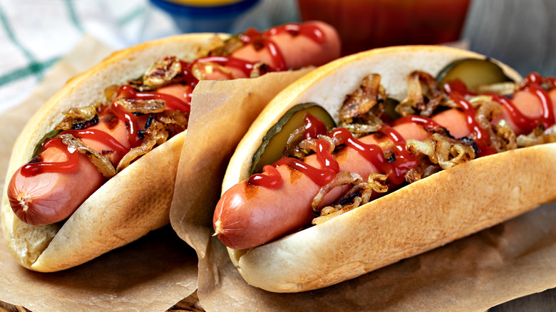 Two hot dogs with ketchup, onions and gherkins