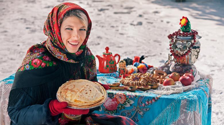 woman celebrating Maslenitsa festival with pancakes