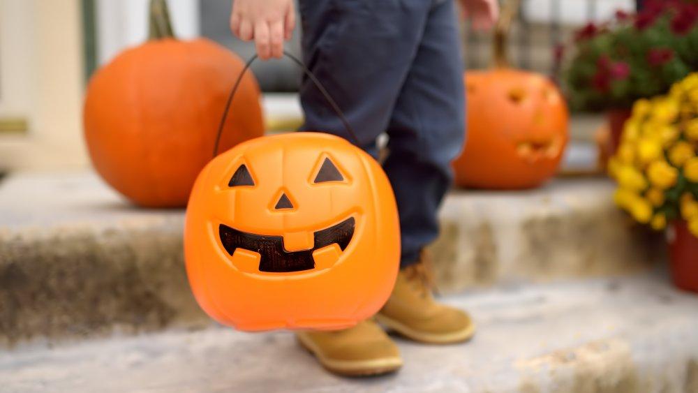 child on steps with a Halloween pumpkin bucket