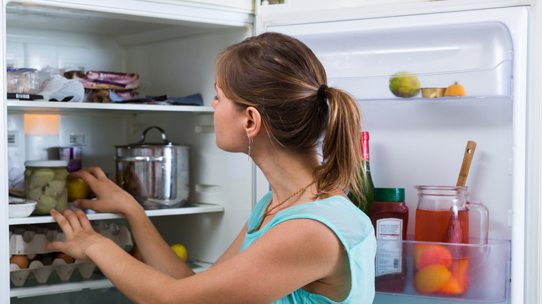 Woman organizing inside of refrigerator