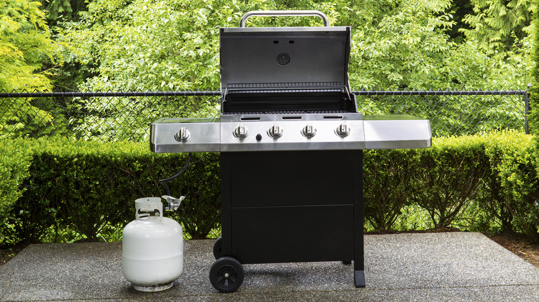 A propane tank next to a gas grill