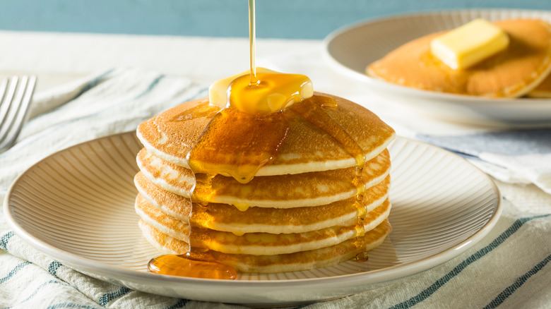 Syrup getting poured over a stack of pancakes