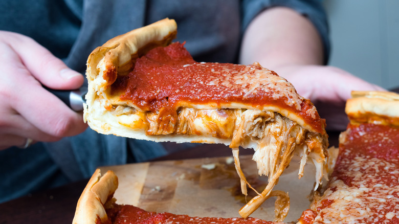 Cutting a slice of deep dish pizza