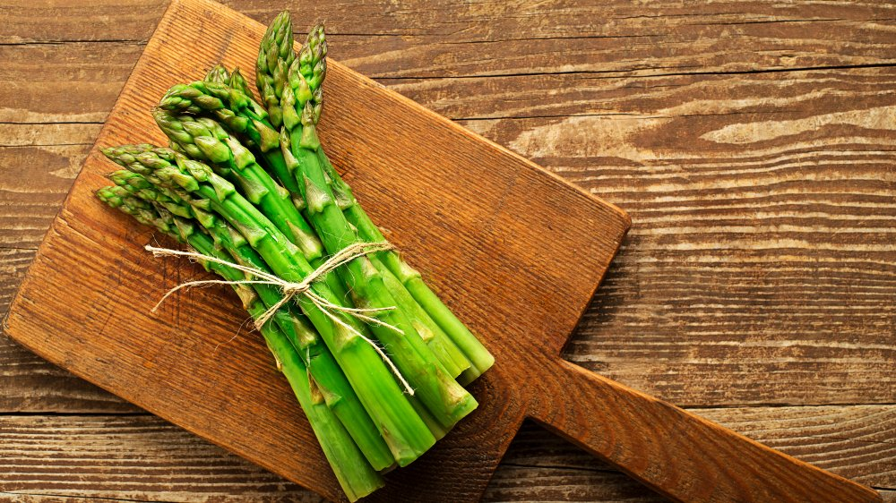 bunch of asparagus on wood cutting board