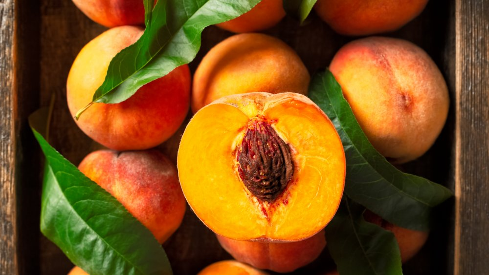 Ripe peaches in box with leaves, one cut in half