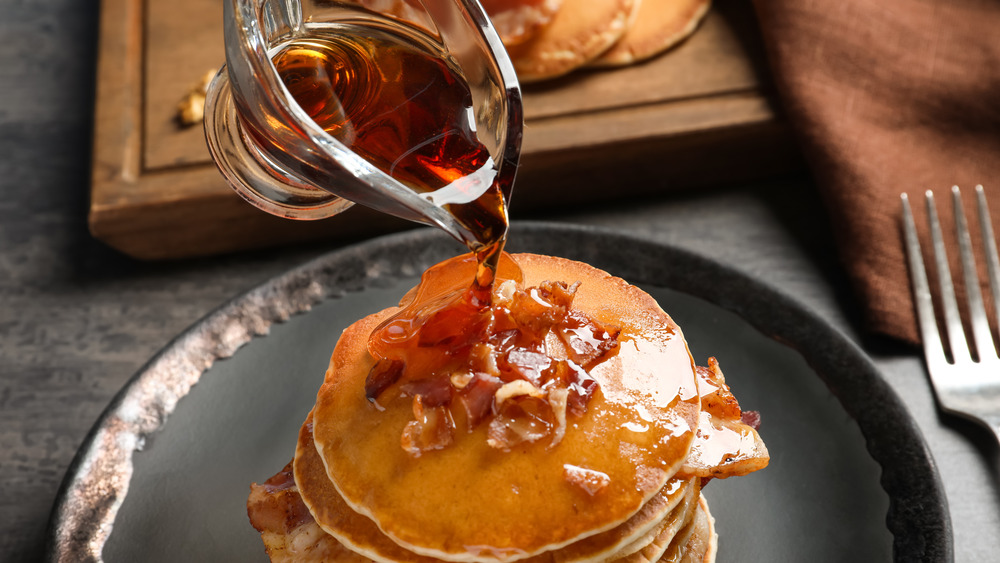 Syrup being poured on pancakes