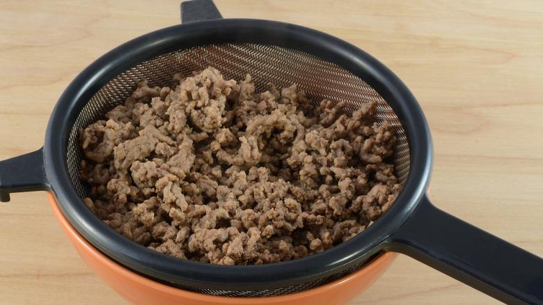 Ground beef in a strainer