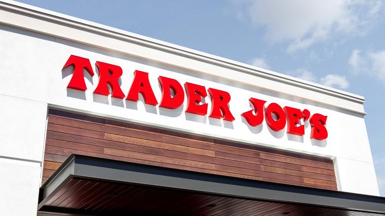 Red Trader Joe's logo on white building against blue sky