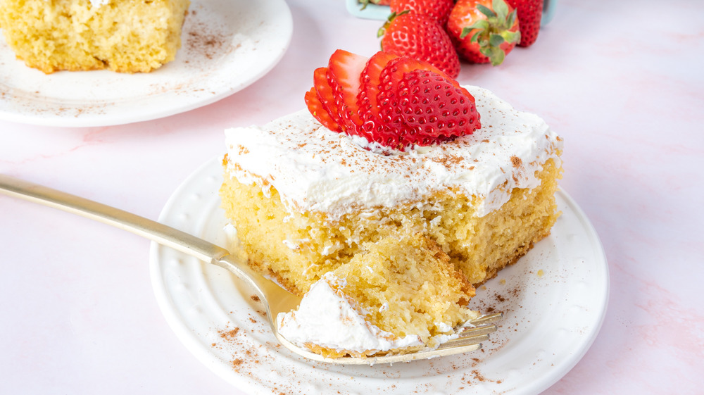 taking a bite from a slice of tres leches cake