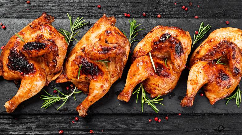 Chicken with crispy brown skin and rosemary garnish