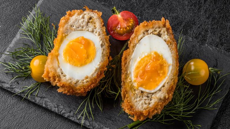 Scotch eggs with garnish on black slab