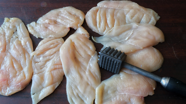 Flattened chicken breasts and a meat tenderizer