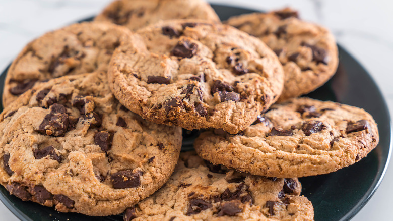 Pile of chocolate chip cookies on black plate