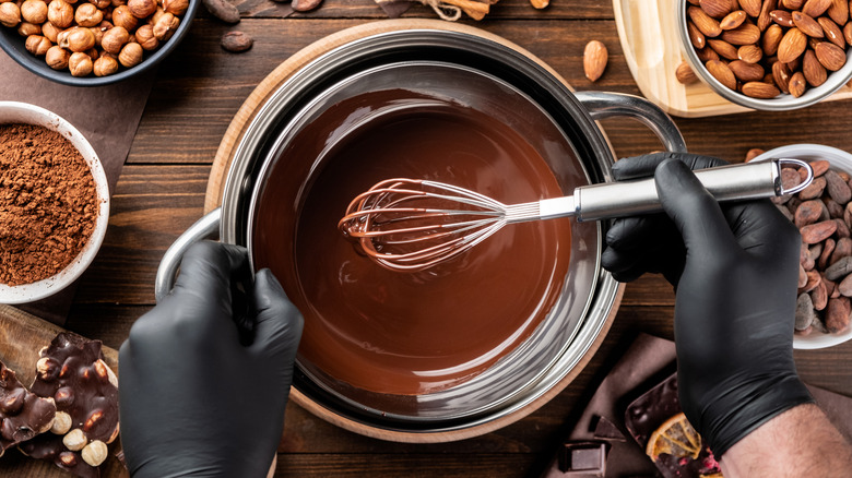 Confectioner stirring melted chocolate in bowl