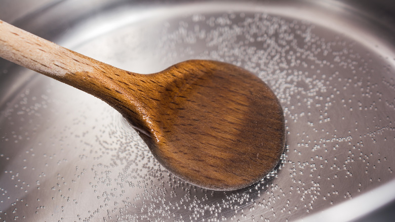 placing a wooden spoon in simmering water