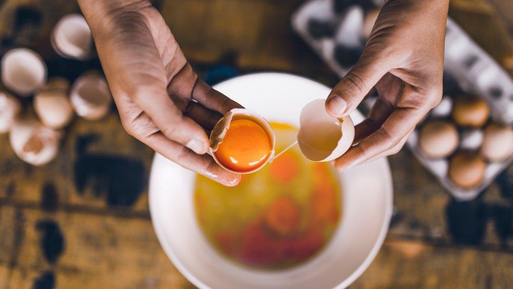 hands separating egg yolks from egg whites