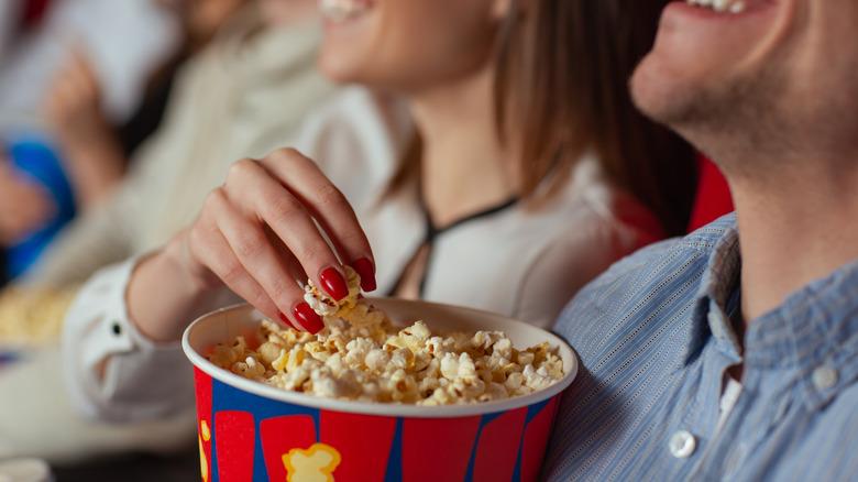 Couple enjoying popcorn at theater