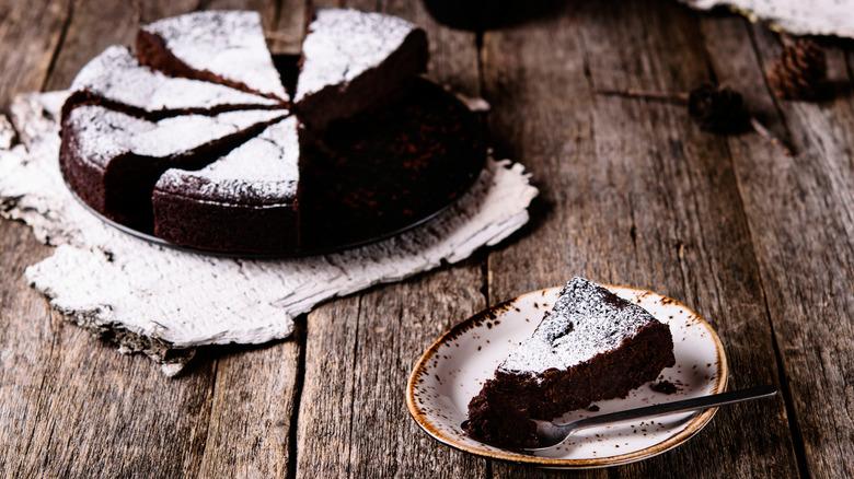 Sliced chocolate cake with powdered sugar on top